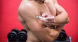 Muscular man injecting steroids in crossfit gym