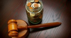 legal gavel with coins in a jar